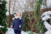 Cute happy child girl in owl hat and blue coat walking in winter snowy garden — Stock Photo