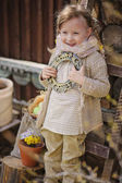 Cute happy child girl in early spring garden holding vintage frame — Stock Photo