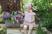 Cute happy child girl in pink plaid dress and flower headband making lilac wreath in spring garden — Stock Photo