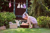 Cute child girl in pink plaid dress plays toy wash in summer garden — Stock Photo