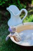 Grey teddy bear washing in foamy water and white jar on green lawn in summer garden — Stock Photo