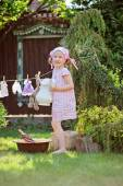 Cute happy child girl in pink plaid dress and flower headband playing toy wash in summer sunny garden — Stock Photo