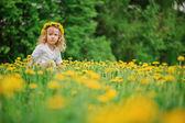 Cute happy child girl in dangelion wreath having fun on spring flower field — Stock Photo