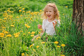 Cute blonde child girl having fun on spring dangelion field — Stock Photo