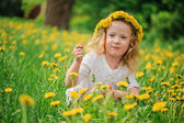 Cute happy child girl in dangelion wreath having fun on spring flower field — Stock Photo