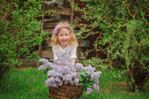 Cute blonde child girl having fun in spring garden with basket of lilacs — Stock Photo