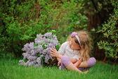 Roztomilá blondýnka dítě dívka v jarní zahradě s košíkem šeřík baví — Stock fotografie