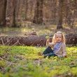 Cute blonde child girl sitting in early spring forest with green leaf — Stock Photo #60764199