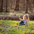 Cute blonde child girl sitting in early spring forest with green leaf — Stock Photo #60764201