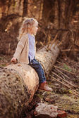 Cute happy blonde child girl in knitted sweater and blue shirt walking in early spring forest — Stock Photo