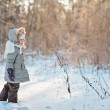 Horizontal portrait of beautiful happy child girl looking out of camera on the walk in winter sunny snowy forest — Stock Photo #61941625