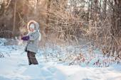 Cute child girl holding snow on the walk in winter snowy sunny forest — Stock Photo