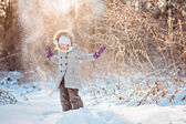 Happy child girl throwing snow on the walk in winter sunny forest — Stock Photo