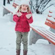Portrait of cute child girl in red coat and white hat on the walk in winter snowy park — Stock Photo #61978469