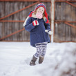 Cute child girl having fun on the walk in winter snowy garden with christmas candy — Stock Photo #62034325