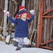 Cute happy child in christmas hat girl throwing snow and having fun in winter snowy garden — Stock Photo #62034355