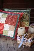 Handmade patchwork red cushion with sewing tools and twig on wooden table — Stock fotografie
