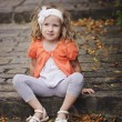 Cute child girl in orange cardigan playing at old stone road with stairs — Stock Photo #62064095