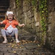 Cute child girl playing and throwing leaves while sitting on old stone road with stairs — Stock Photo #62064097