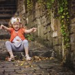 Cute child girl playing and throwing leaves while sitting on old stone road with stairs — Stock Photo #62064111