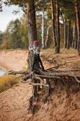 Child girl climbing old pine tree on river side — Stock Photo