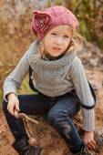 Cute child girl in pink knitted hat vertical portrait at autumn river side with sand beach — Стоковое фото