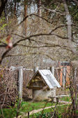 Old rustic water well in early spring garden — Stock Photo