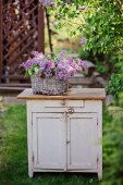 Basket with lilacs bouquet on vintage wooden bureau in spring garden — Fotografia Stock