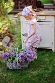 Cute child girl in spring garden with basket of lilacs near vintage wooden bureau — Stock Photo