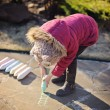 Child girl in pink jacket drawing with chalks in spring garden — Stock Photo #63543653