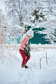 Winter portrait of cute child girl in pink sweater on the walk in winter snowy forest — Stock Photo