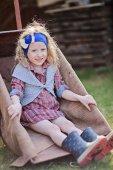 Adorable happy child girl in wheelbarrow in spring sunny garden — Stock Photo