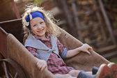 Garota adorável criança feliz no carrinho de mão no ensolarado jardim primavera — Fotografia Stock