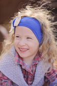 Spring portrait of happy child girl in blue headband — Stock Photo