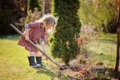 Cute child girl helps in spring garden with shovel — Stock Photo