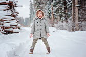 Child girl having fun on the walk in winter snowy forest with tree felling on background — Stock Photo