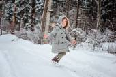 Child girl running on the walk in winter snowy forest — Stock Photo
