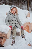 Child girl in winter forest sitting on wood log — Zdjęcie stockowe