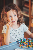 Cute preschooler girl plays with mosaics at home — Stock Photo