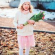 Child girl with tulips bouquet on the walk in early spring day — Stock Photo #66160528