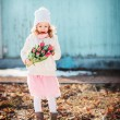 Child girl with tulips bouquet on the walk in early spring day — Stock Photo #66160580