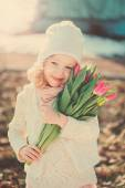 Spring vintage tones portrait of happy child girl with tulips bouquet for woman's day — Stock Photo
