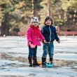 Toddler boy and girl having fun and playing paper boats in spring puddle — Stock Photo #68039495