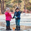 Toddler boy and girl having fun and playing paper boats in spring puddle — Stock Photo #68039501