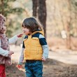 Happy toddler girl giving cookie to her friend on the walk in forest — Stock Photo #68418995