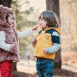 Happy toddler girl giving cookie to her friend on the walk in forest — Stock Photo #68419015
