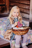 Adorable happy child girl with decorations for easter at wooden country house — Stock Photo
