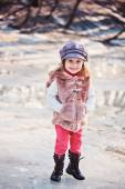 Happy toddler girl portrait on the walk in early spring with melting ice on background — Stockfoto