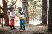 Toddler friends are happy playing whirligig in sunny forest — Stock Photo