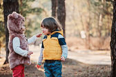 Happy toddler girl giving cookie to her friend on the walk in forest — Stock Photo